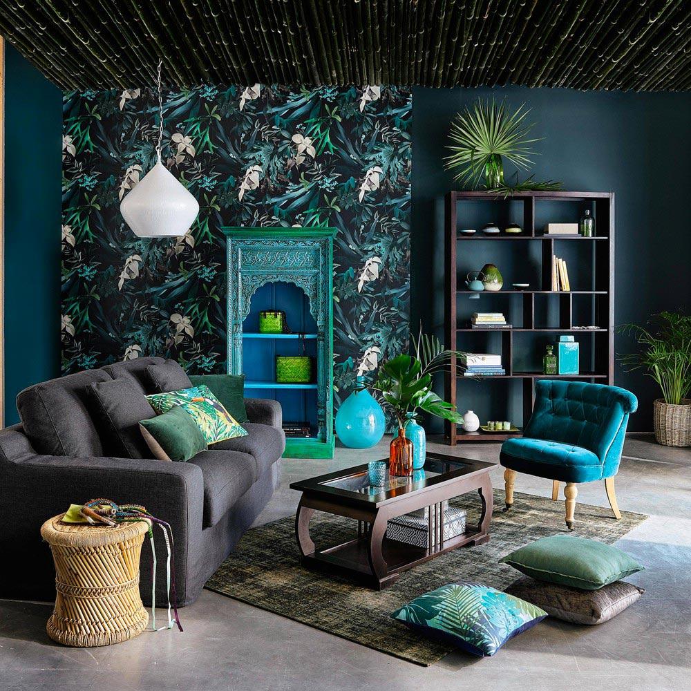 Soggiorno arredato con colori forti e scuri: verde Ottavio e fantasie floreali stile giungla.