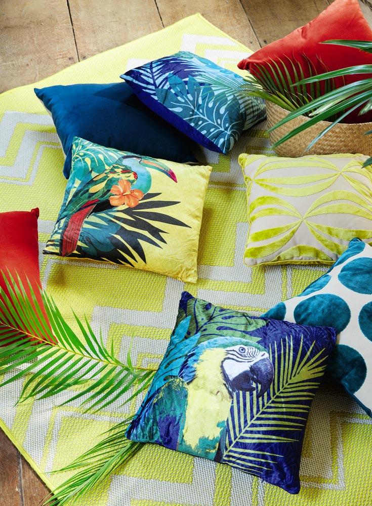 Cuscini coloratissimi con stampe di uccelli tropicali.