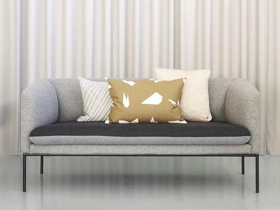 Divano grigio con composizione di cuscini geometrici oro e beige.