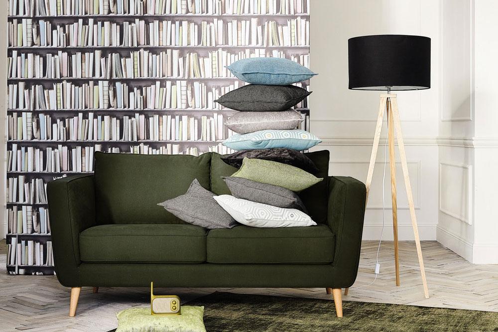 Divano vintage verde scuro con pila di cuscini appoggiata sopra.