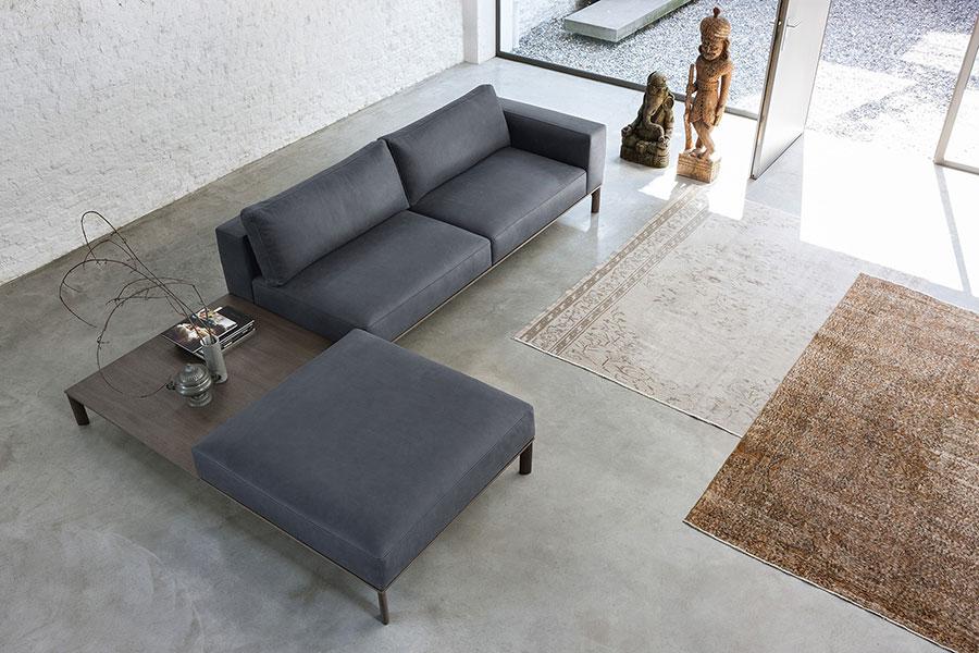Place di Doimo Salotti - divano in pelle in composizione con tavolino ad angolo e pouf.