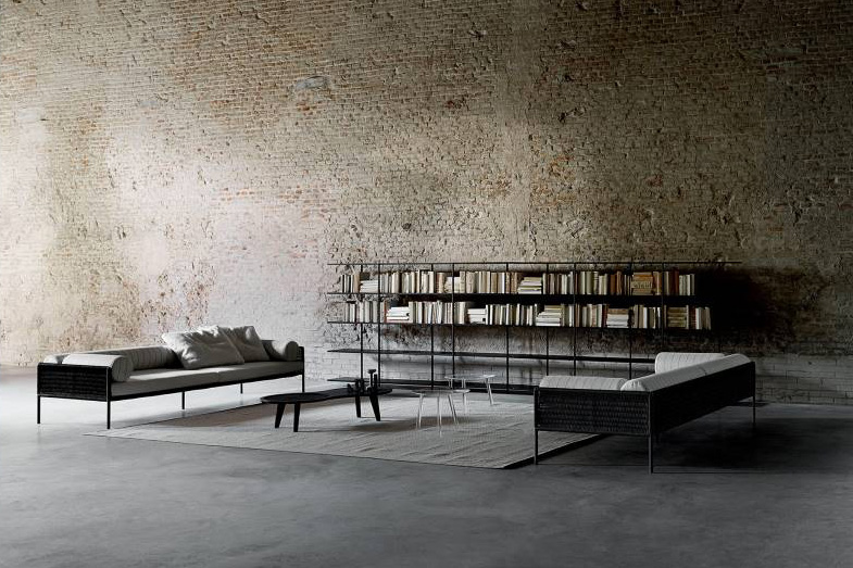 Living divani modello Agra, salotto con piedini sottili e libreria minimale.