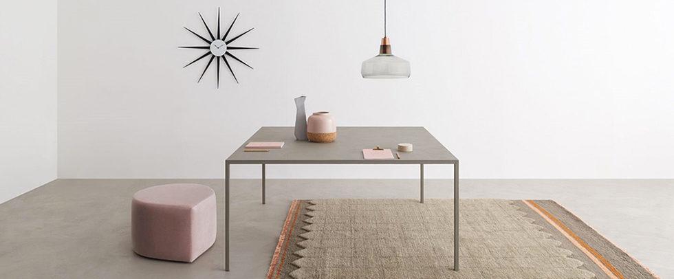 Desalto tavolo modello Helsinki grigio con vasi e pouf rosa.