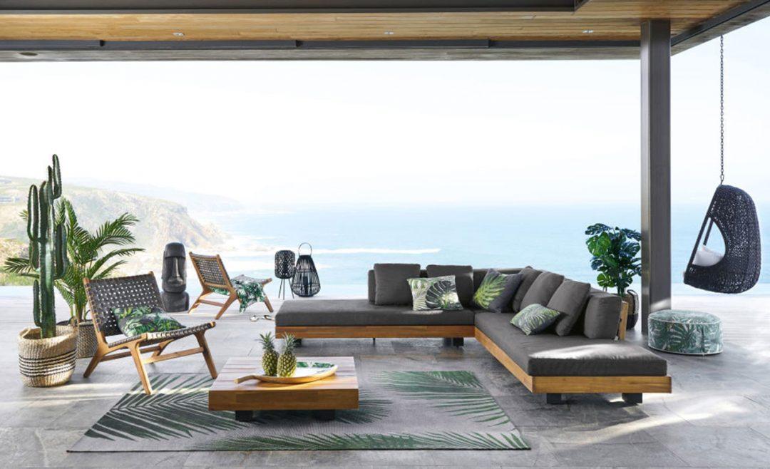 divano da esterno grigio con cuscini stampa tropicali